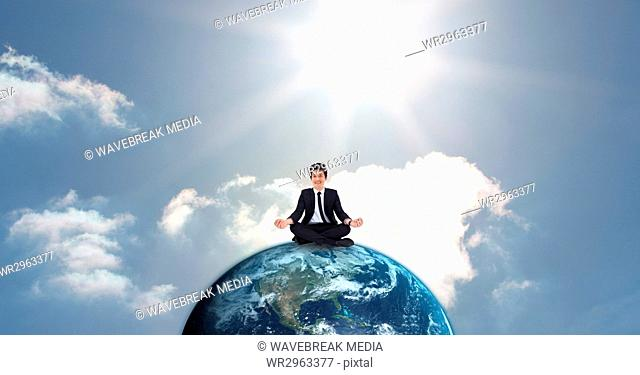Businessman meditating on globe against sky