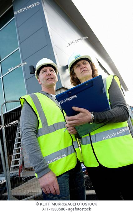 Two people making a health and safety inspection report on a construction site UK