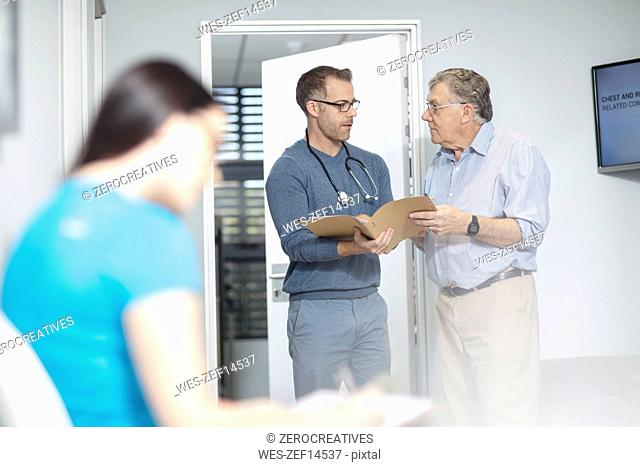 Doctor with file talking to patient in medical practice