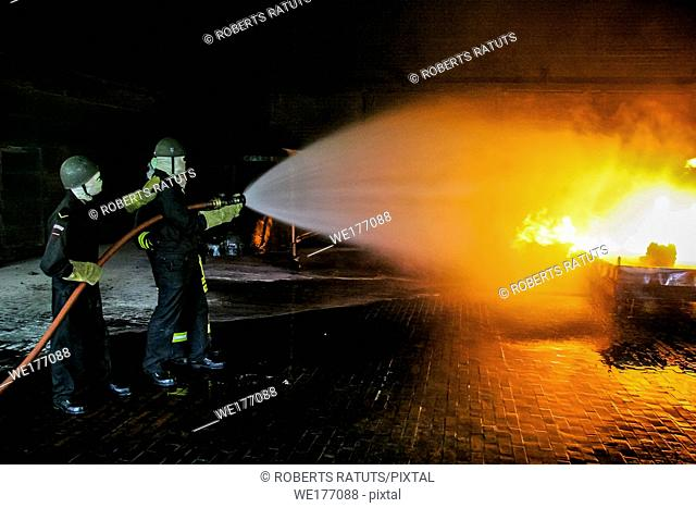 Firefighters training for fire fighting in Germany. Firefighter in fire protection suit spraying water to fire with smoke