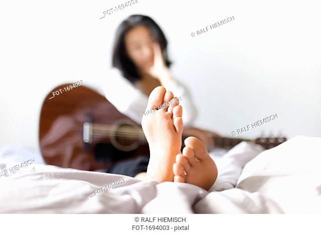Woman with bare feet holding guitar while resting on bed at home