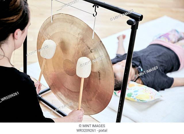 Woman striking a large gong with soft drumsticks during a sound therapy session