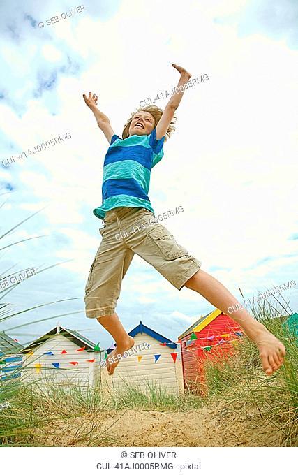 Boy jumping for joy on sandy beach