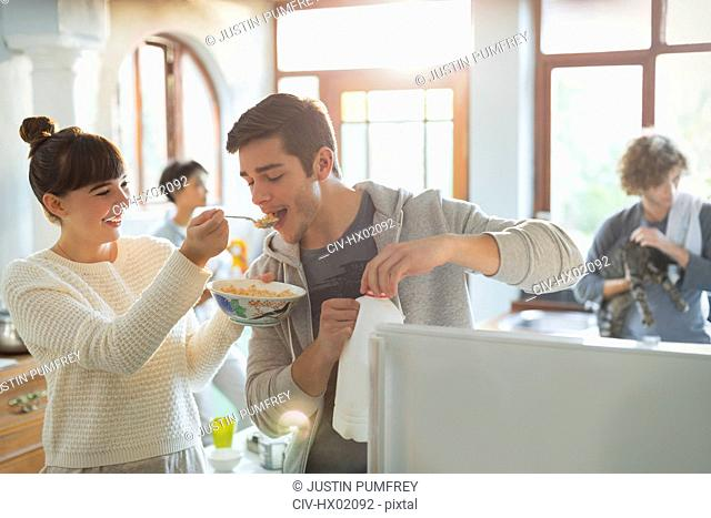 Young woman feeding boyfriend cereal in apartment kitchen