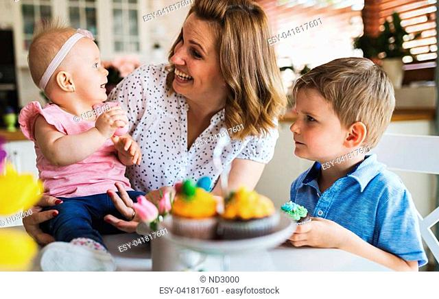 Easter concept. Happy and loving mother and her kids preparing home decoration