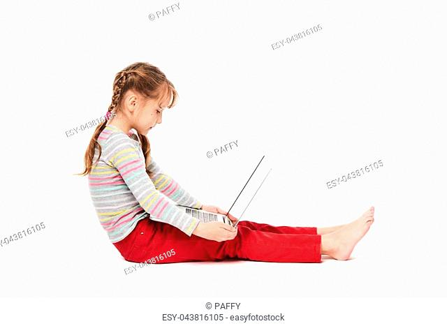 Smiling little girl sitting on the floor with laptop, showing blank black screen, over white background