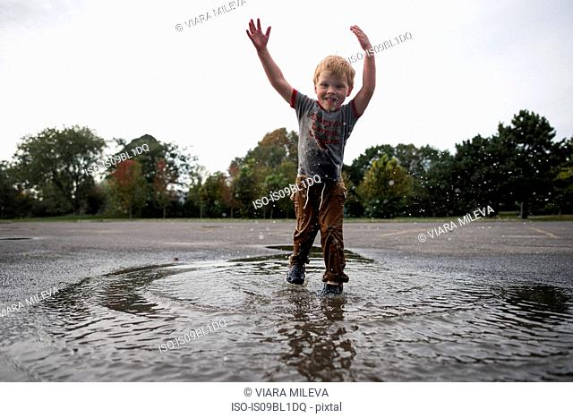 Boy playing in puddle on road