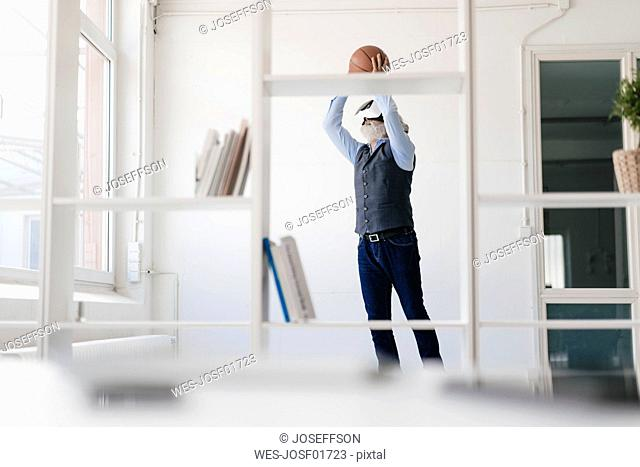Mature man wearing VR glasses playing basketball in office