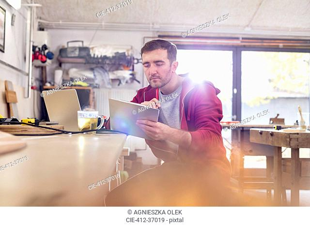 Male carpenter using digital tablet, drinking tea at workbench in workshop