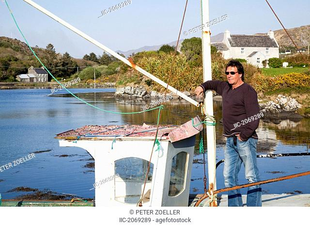 A Man Stands On An Old Fishing Boat Near Eyeries, County Cork Ireland