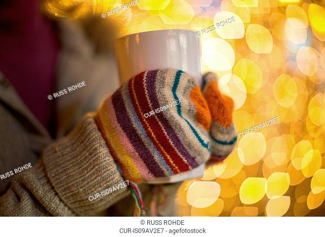 Close up of woman hands wearing mittens holding hot drink in front of xmas lights