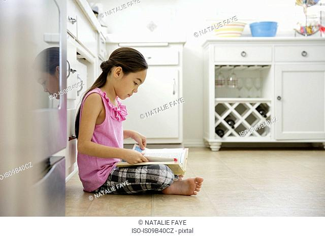 Girl sitting on kitchen floor reading book