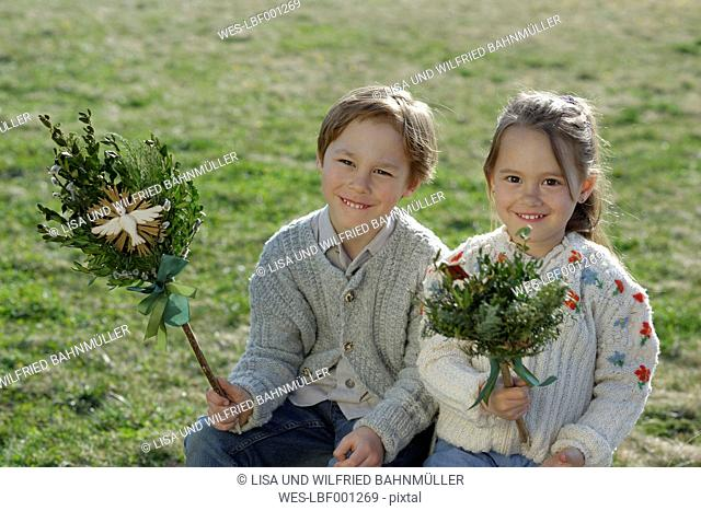 Germany, Upper Bavaria, little boy and girl with Palmbusch on a meadow