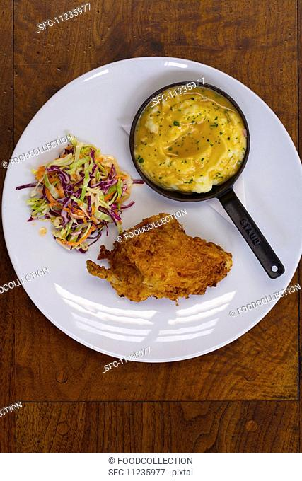 Fried chicken with mashed potatoes, gravy and a side of coleslaw