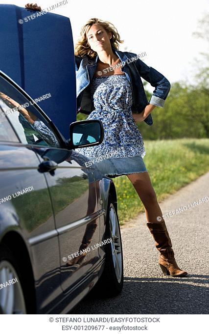 Beautiful woman standing by her broken car