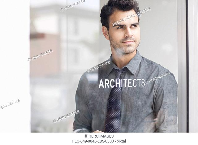 serious young architect standing behind window