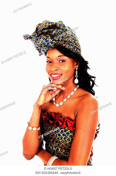 A beautiful African American woman in an African style dress with her.hand under her chin, isolated for white background.