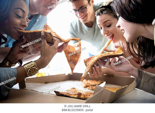 Friends eating slices of pizza