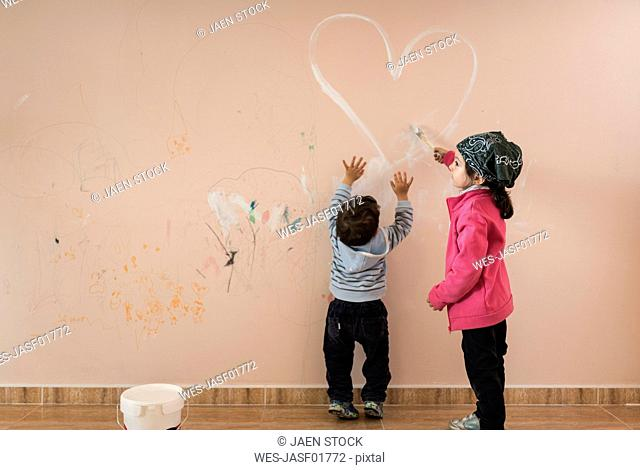 Little girl painting on wall in children's room while her brother watching