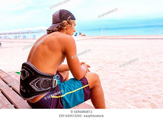 Young attceractive guy surfer sits with his back to the camera on the terrace on the beach looking out into the distance to the see