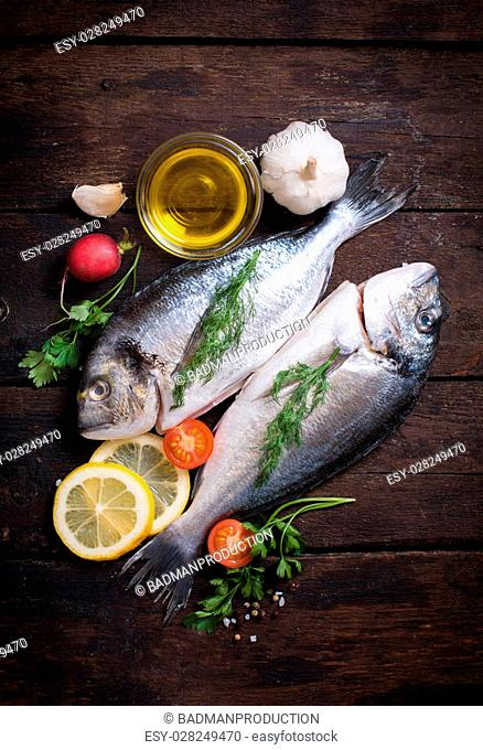 Raw dorada fish with ingredients on wooden background