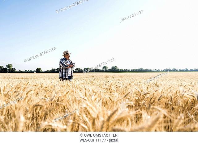 Happy senior farmer standing in wheat field