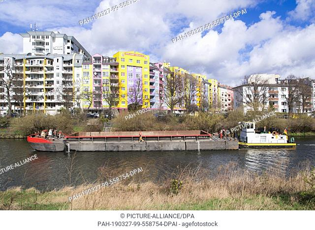 """25 March 2019, Berlin: A cargo ship with the tug """"""""Triton"""""""" sails against the backdrop of the colourful facades of residential buildings on the north bank"""