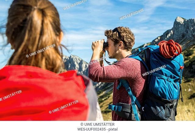 Austria, Tyrol, Tannheimer Tal, young man on hiking trip looking through binocular