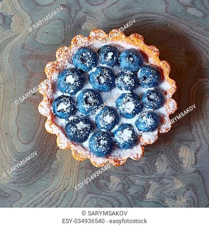 Tartlet with fresh blueberries. Background with copy space