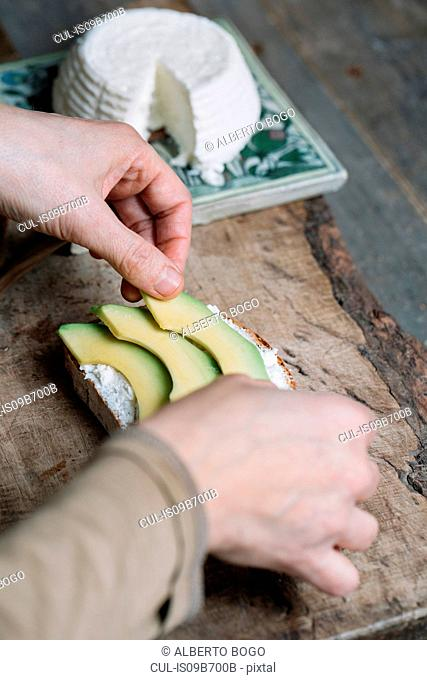 Woman placing slices of avocado onto sliced bread with ricotta, close-up