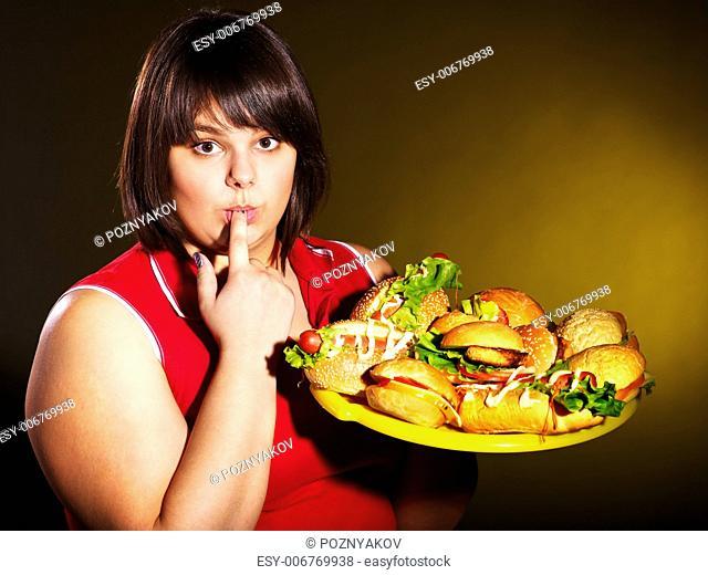 Overweight woman eating hamburger