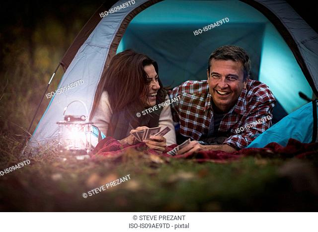 Mature couple lying together in tent, playing card game