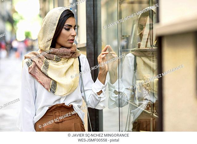 Spain, Granada, young muslim tourist woman wearing hijab looking at shop windows on a shopping street