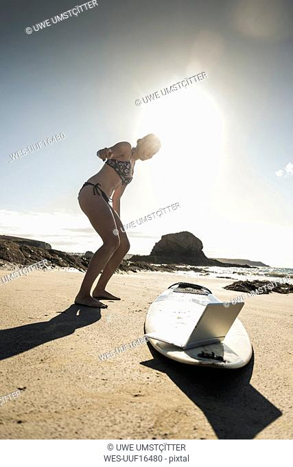 Young woman standing by surfboard, using laptop