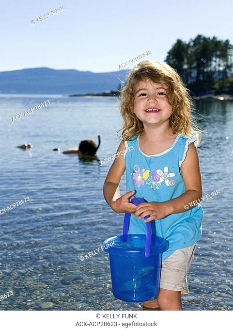A young girl takes time out from playing, while her father snorkels in the Pacific Ocean, near Powell River, on the Sunshine coast of the Vancouver coast and...