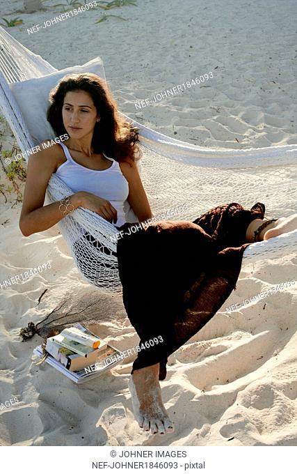 Young woman resting on hammock on beach