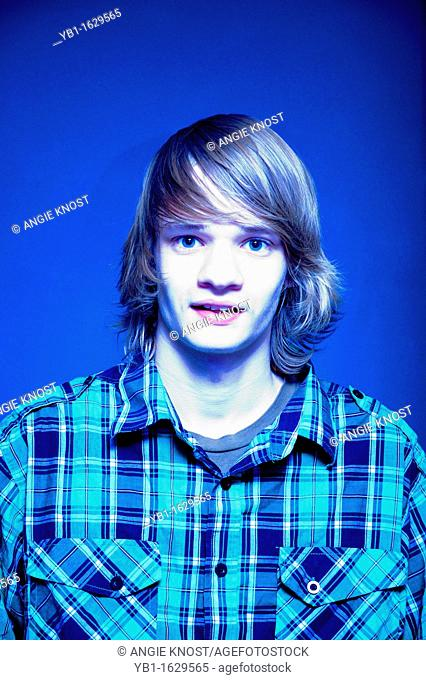 Portrait of a teenage boy, age 16 years, with long blond hair  Photo has cross-coloring effect