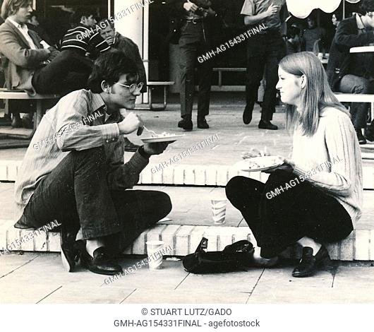 A male and female student, both wearing hippie attire, sit together on steps during an anti Vietnam War student sit-in protest at North Carolina State...