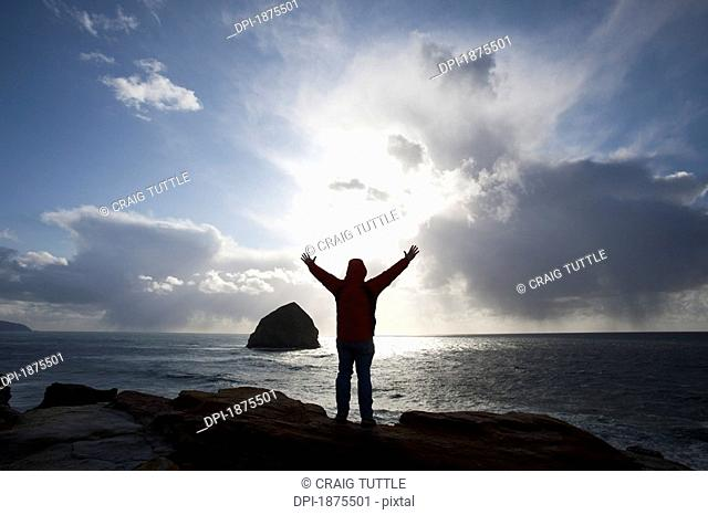 oregon, united states of america, silhouette of a person lifting their hands standing at cape kiwanda cliffs with a view of haystack rock