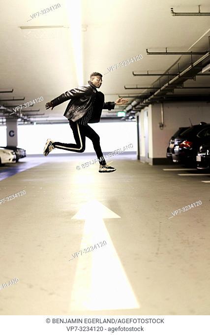 man jumping in parking garage, in Munich, Germany