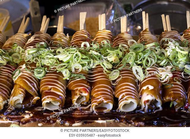 Kyoto, Japan - Baking Hashimaki, okonomiyaki on sticks with fresh spring onions as a snack