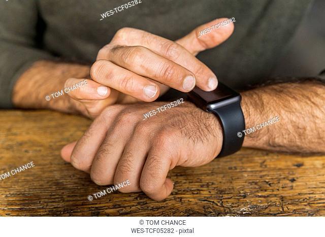 Close-up of man using smartwatch