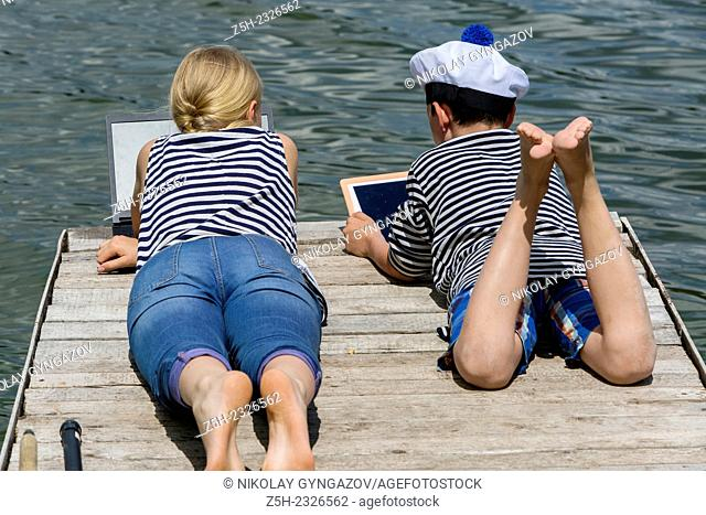 Boy and girl of twelve years in a sailor uniform with a laptop on the dock