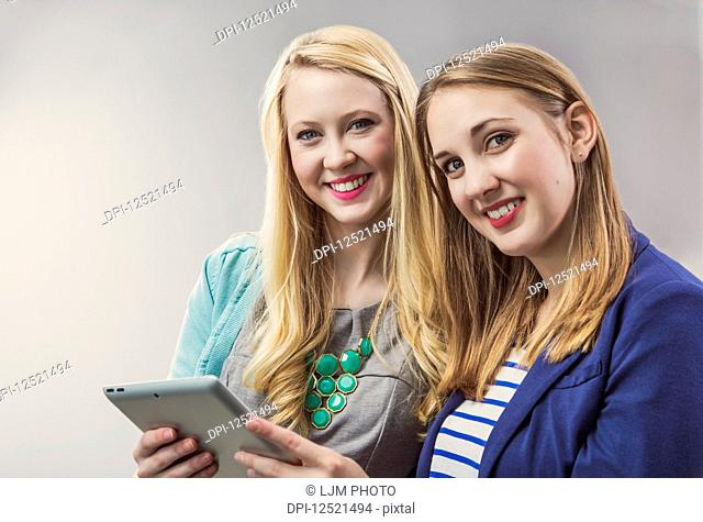 Two beautiful young women who are millennial business professionals working together using a tablet and posing for the camera at their workplace; Sherwood Park