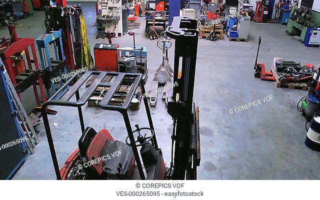 Vertical dolly up through a large mechanics workshop