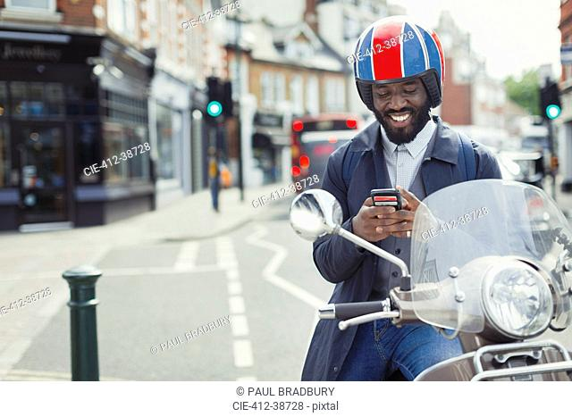 Smiling young businessman in helmet on motor scooter texting with cell phone on urban street