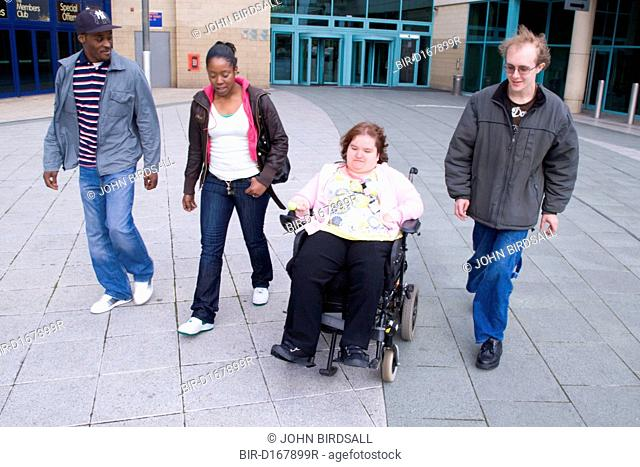 Group of friends, including a young woman who is a wheelchair user, leaving a public building together