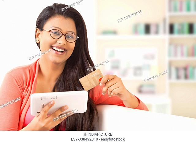 Woman using credit card online with a mobile phone