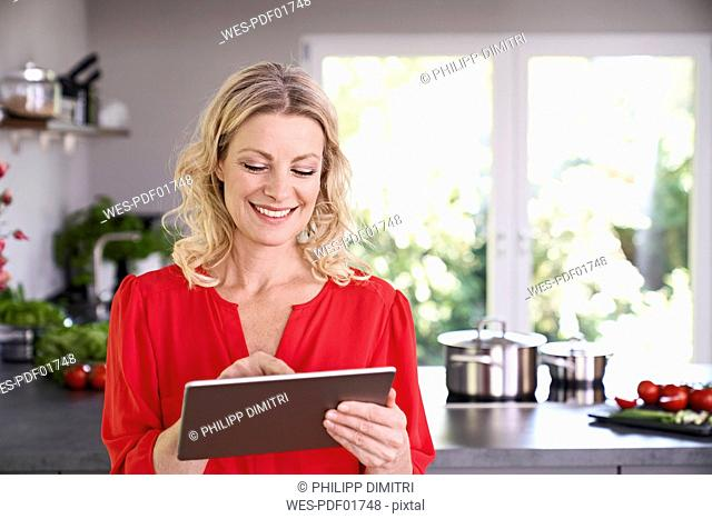 Smiling woman using tablet in kitchen