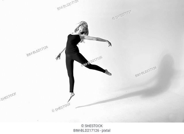 Caucasian dancer jumping for joy